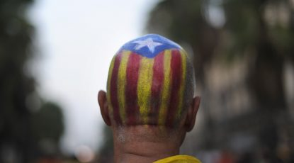 BARCELONA, SPAIN - SEPTEMBER 11:  A man with a Pro-independence Catalan flag painted on his head stands during a demonstration calling for independence during the Catalonia's National Day on September 11, 2012 in Barcelona, Spain. Thousands of Catalans took to the streets of Barcelona demanding a split from Spain and control of their own economy under the slogan 'Catalonia: New European State' on Catalonia's National Day. The Diada Nacional is held every September 11 to remember the defeat of the Catalan troops in 1714.  (Photo by David Ramos/Getty Images)